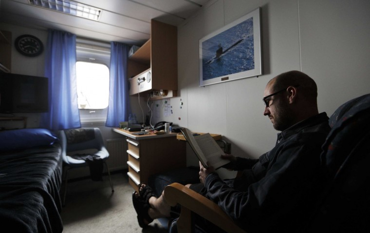 In this Sunday, July 9, 2017 photo, boatswain Henri Helminen reads a book in his cabin after working a shift aboard the Finnish icebreaker MSV Nordica as it sails the North Pacific Ocean to traverse the Northwest Passage through the Canadian Arctic Archipelago. (AP Photo/David Goldman)