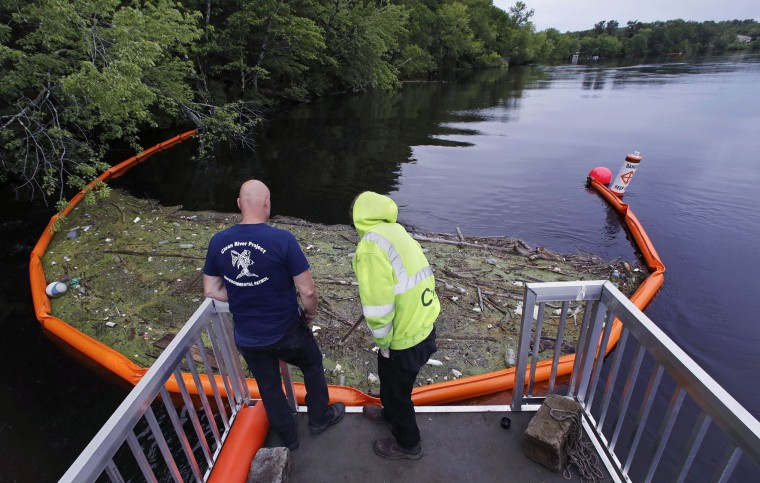 "In this Wednesday, June 7, 2017 photo, activist Rocky Morrison, left, and volunteer Dalton Abbott, of the ""Clean River Project"" examine a boom filled with waste collected from a recovery boat on the Merrimack River in Chelmsford, Mass. Syringes left by drug users amid the heroin crisis are turning up everywhere. They hide in weeds along hiking trails and in playground grass, get washed into rivers and onto beaches, and lie scattered about in baseball dugouts and on sidewalks and streets. There are reports of children finding them and getting poked. (AP Photo/Charles Krupa)"