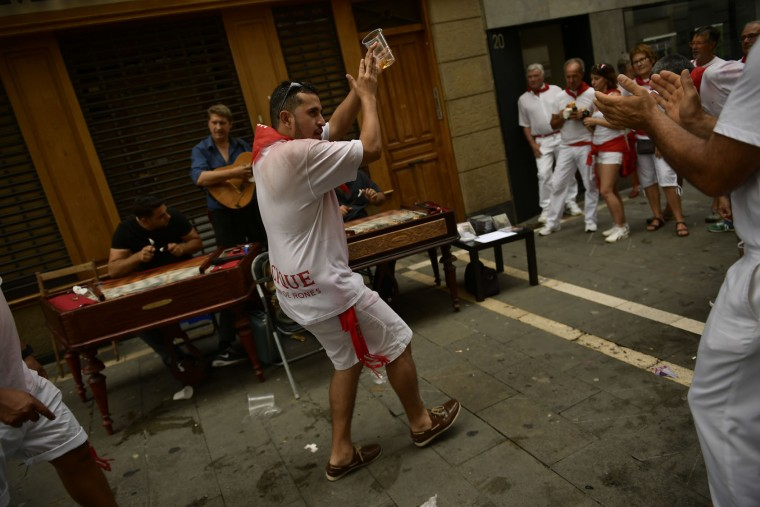 A reveller dances in the street after the launching of the 'Chupinazo' rocket, to celebrate the official opening of the 2017 San Fermin Fiestas in Pamplona, Spain, Thursday July 6, 2017. The first of eight days of the running of the bulls along the streets of the old quarter of Pamplona starts Friday. (AP Photo/Alvaro Barrientos)