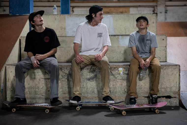(L-R) Alex Flores, 14, Noah Wingard, 15, and Trent Harper-Jett, 12, take a quick break from skateboarding inside the Charm City Skatepark in Baltimore on Friday, July 7, 2017. (Michael Ares / The Baltimore Sun)