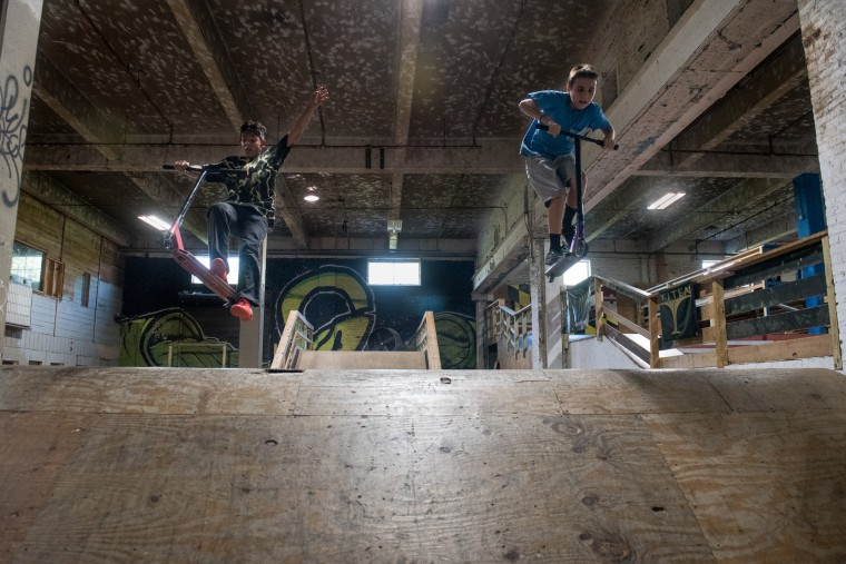 Nick Dicara, 13, left, and Skyler Hubbard, 11, right, ride scooters over a ramp inside the Charm City Skatepark in Baltimore on Friday, July 7, 2017. (Michael Ares / The Baltimore Sun)