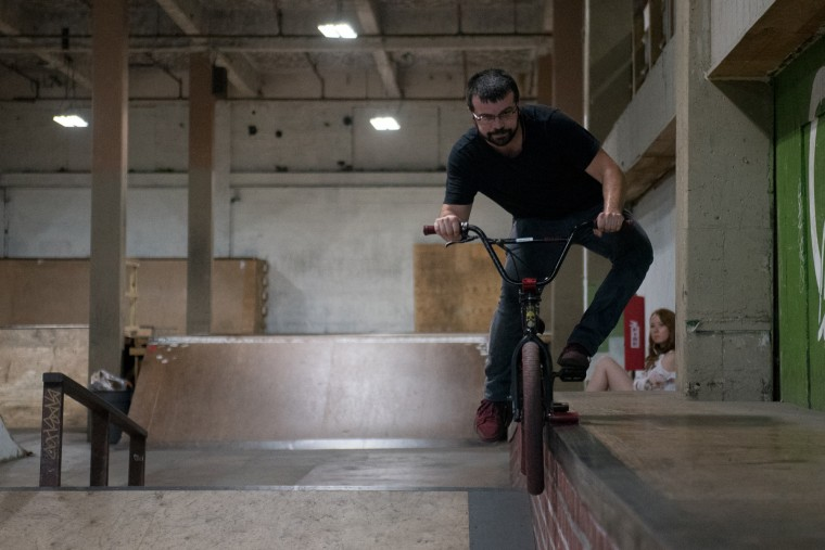John Hock, owner of John's Bicycle Repair located inside Charm City Skatepark, slides his bike on a ledge in Baltimore on Friday, July 7, 2017. (Michael Ares / The Baltimore Sun)