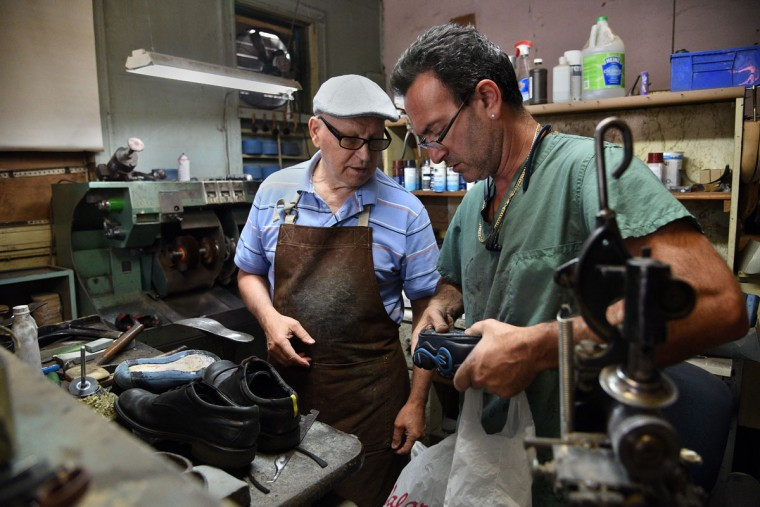 Leonid Boryachinsky, left, and Eugene Gomberg, right, look at a pair of shoes that need repair. Mr. Gomberg is owner of ESG Shoe Repair in Roland Park and has been a cobbler for 25 years. Mr. Boryachinsky, a friend, helps out in the shop when things get busy. (Barbara Haddock Taylor/ Baltimore Sun)