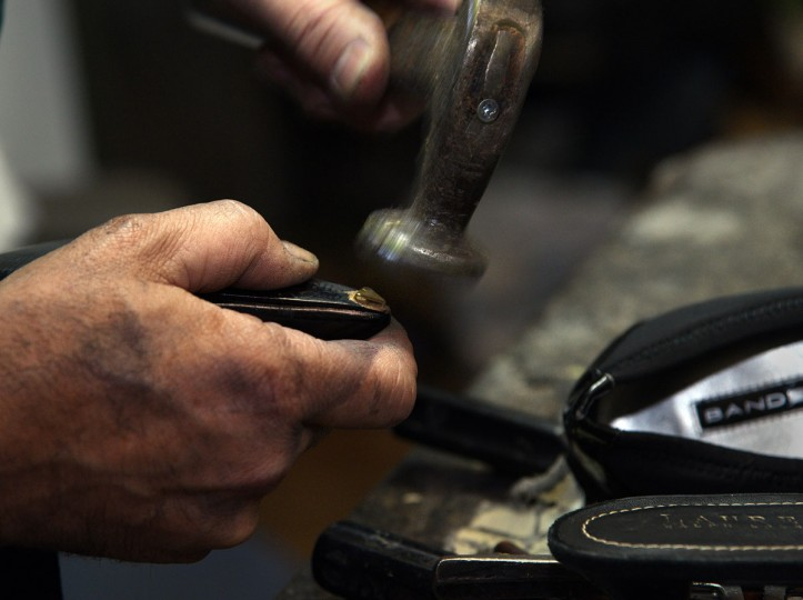 Eugene Gomberg uses a shoe hammer on a pointy-toed shoe in his shop. (Barbara Haddock Taylor/ Baltimore Sun)