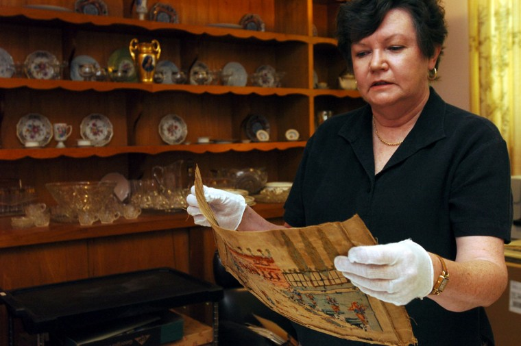 HALETHORPE, MD--6/17/04--Sharon Knecht, project archivist, looks over a needlework sampler made by Harriett Cooper in 1843. Cooper was taught by Oblate Sisters of Providence in the early days of the order that began 175 years ago in Baltimore. (Kim Hairston/Baltimore Sun archives)
