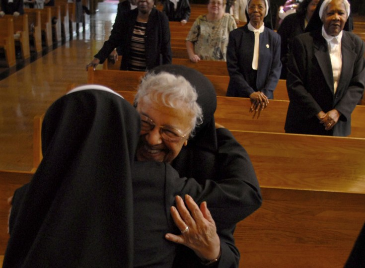"CATONSVILLE, MD -- 3/25/09 -- Sister Mary Alice Chineworth, OSP, 91 (she will be 92 in July) (RT), gives Sister Mary Anthonia Nwoga, a Nigerian-born woman in her 40s (LT) a hug after the ""Presentation of the Veil"". Liturgy of the Eucharist and Rite of First Profession for Sister Anthonia Nwoga was held at the Oblate Sisters of Providence. This is a big deal for an order that has seen its numbers decline steadily for years as nuns die off and aren't replenished with new arrivals. The Oblate Sisters of Providence was founded in Baltimore in 1829 and is the first Roman Catholic religious order made up entirely of African American women. The taking of the black veil means Anthonia will go from ""novice"" to ""professed sister,"" and she'll then have five years to decide whether to make her ""final vows."" The point is this is a big step toward becoming a lifelong member of the order. (CHIAKI KAWAJIRI/Baltimore Sun)"