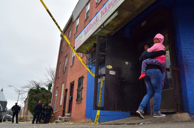 """A woman carries a child into the Mini Market while police investigate a shooting on E. Eager Street in January 2017."" (Photo and caption courtesy of Maggie Ybarra)"