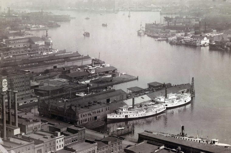 The steamships 'Avalon' and 'Eastern Shore' are docked in Baltimore's inner harbor in the early 1900s. The photo was taken from the top of the National Bank Building on Light street.