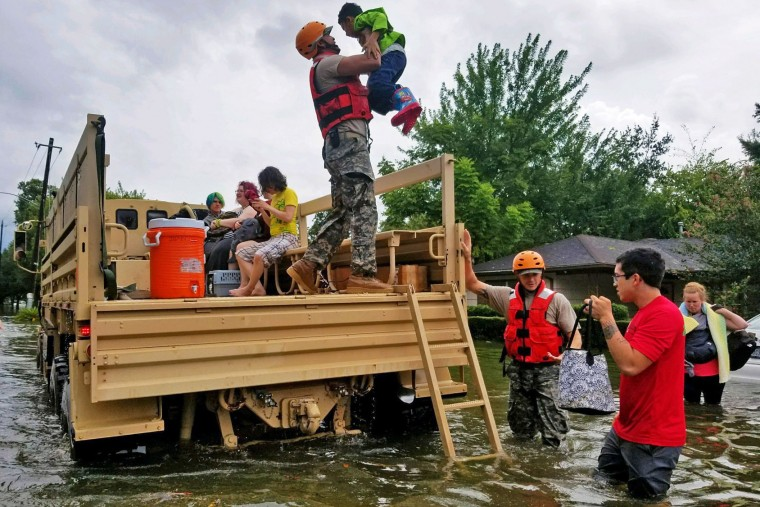 HOUSTON, TX - AUGUST 27: In this handout provided by the Army National Guard, Texas National Guardsmen assist residents affected by flooding caused by Hurricane Harvey onto a military vehicle August 27, 2017 in Houston, Texas. Harvey, which made landfall north of Corpus Christi late Friday evening, is expected to dump upwards to 40 inches of rain in areas of Texas over the next couple of days. (Photo by Lt. Zachary West/Army National Guard via Getty Images)