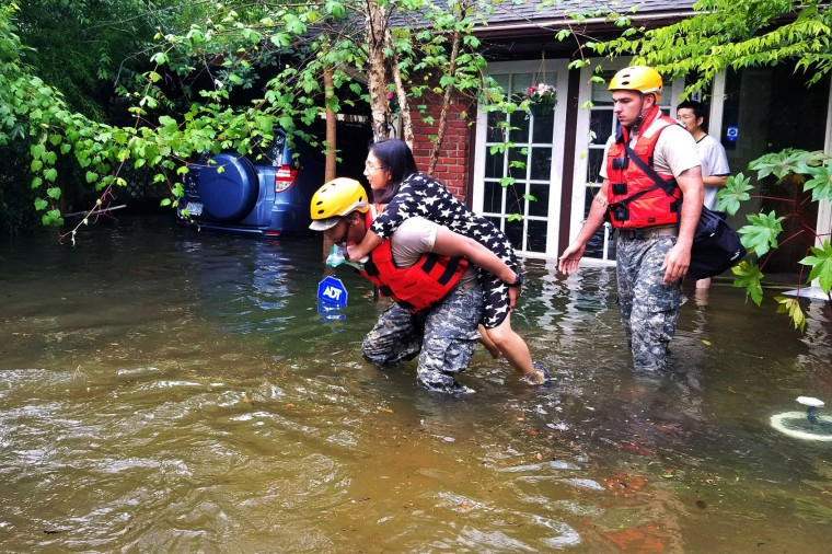 HOUSTON, TX - AUGUST 27: In this handout provided by the Army National Guard, A Texas National Guardsman carries a resident from her flooded home following Hurricane Harvey August 27, 2017 in Houston, Texas. Harvey, which made landfall north of Corpus Christi late Friday evening, is expected to dump upwards to 40 inches of rain in areas of Texas over the next couple of days. (Photo by Lt. Zachary West/Army National Guard via Getty Images)