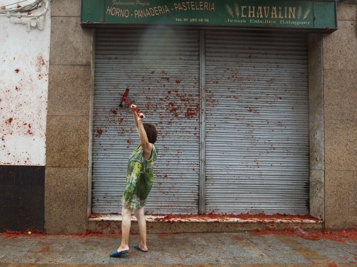 "A woman cleans the front door for a pastry shop during the annual ""Tomatina"" festival in the eastern town of Bunol, on August 30, 2017. The iconic fiesta -- which celebrates its 72nd anniversary and is billed at ""the world's biggest food fight"" -- has become a major draw for foreigners, in particular from Britain, Japan and the United States. (JAIME REINA/AFP/Getty Images)"