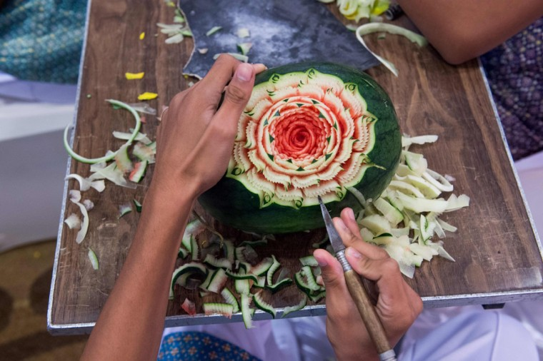 A Thai boy carves floral patterns into a watermelon during a fruit and vegetable carving competition in Bangkok on August 4, 2017. It is a royal tradition that has proved bountiful through the ages and one that Thailand's fruit carvers are determined to keep alive -- even as young people peel away from the unique art form. (ROBERTO SCHMIDT/AFP/Getty Images)