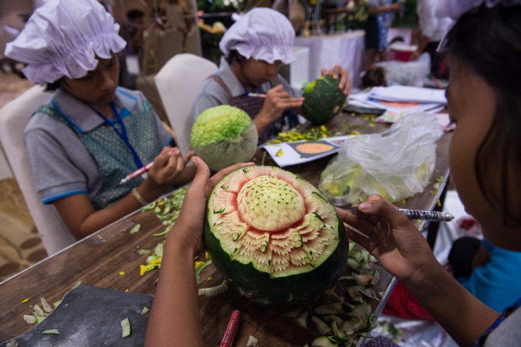 Thai girls carve floral patterns into fruits during a fruit and vegetable carving competition in Bangkok on August 4, 2017. It is a royal tradition that has proved bountiful through the ages and one that Thailand's fruit carvers are determined to keep alive -- even as young people peel away from the unique art form. (ROBERTO SCHMIDT/AFP/Getty Images)