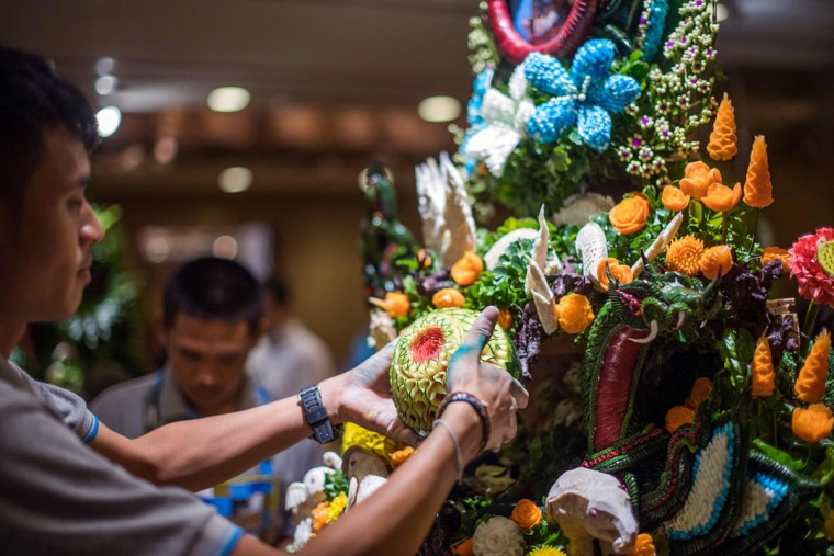 A Thai man helps put together an elaborate decoration with carved fruits and vegetables during a fruit and vegetable carving competition in Bangkok on August 4, 2017. It is a royal tradition that has proved bountiful through the ages and one that Thailand's fruit carvers are determined to keep alive -- even as young people peel away from the unique art form. (ROBERTO SCHMIDT/AFP/Getty Images)