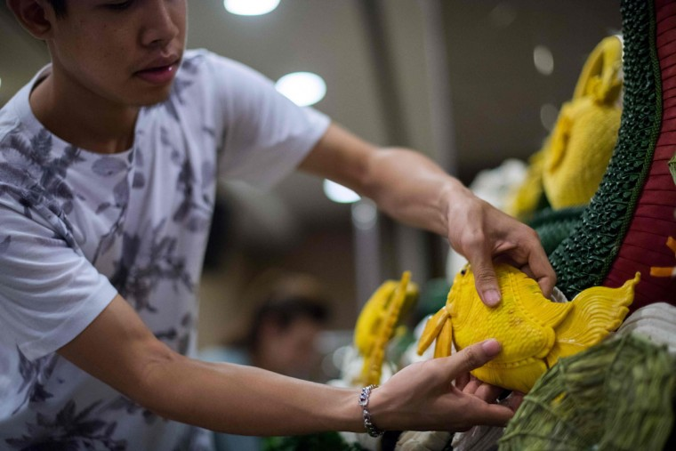 A man adds a pumpkin carved in the shape of a fish to an elaborate display during a fruit and vegetable carving competition in Bangkok on August 4, 2017. It is a royal tradition that has proved bountiful through the ages and one that Thailand's fruit carvers are determined to keep alive -- even as young people peel away from the unique art form. (ROBERTO SCHMIDT/AFP/Getty Images)