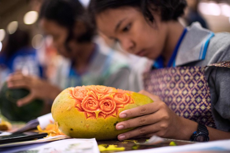 A Thai girl carves floral patterns into a papaya during a fruit and vegetable carving competition in Bangkok on August 4, 2017. It is a royal tradition that has proved bountiful through the ages and one that Thailand's fruit carvers are determined to keep alive -- even as young people peel away from the unique art form. (ROBERTO SCHMIDT/AFP/Getty Images)