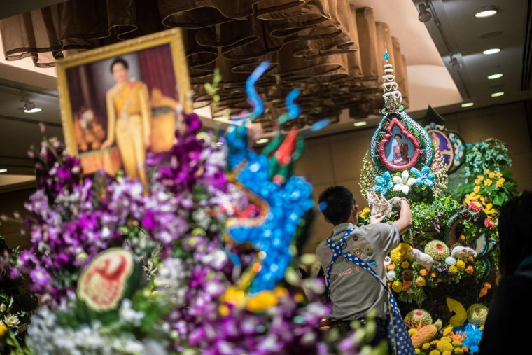 A Thai man helps put together an elaborate decoration with carved fruits and vegetables adorned with images of Thai Queen Sirikit, during a fruit and vegetable carving competition in Bangkok on August 4, 2017. It is a royal tradition that has proved bountiful through the ages and one that Thailand's fruit carvers are determined to keep alive -- even as young people peel away from the unique art form. (ROBERTO SCHMIDT/AFP/Getty Images)