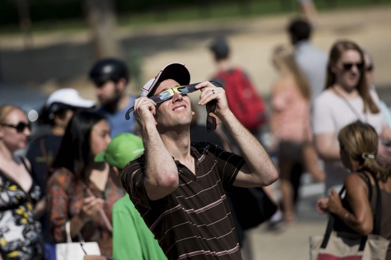 A man tests special solar glasses after getting them outside the Smithsonian's Air and Space Museum on the National Mall before an eclipse August 21, 2017 in Washington, DC. Skygazers across the United States awoke in excited anticipation Monday of witnessing the Sun briefly disappear, with the first total solar eclipse in 99 years to cast a shadow on the entire continent just hours away. (Brendan Smialowski/AFP/Getty Images)