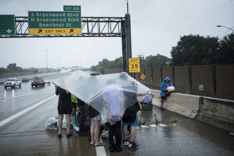 Evacuation residents from the Meyerland wait on an I-610 overpass for further help during the aftermath of Hurricane Harvey August 27, 2017 in Houston, Texas. Hurricane Harvey left a trail of devastation Saturday after the most powerful storm to hit the US mainland in over a decade slammed into Texas, destroying homes, severing power supplies and forcing tens of thousands of residents to flee. (Brendan Smialowski/AFP/Getty Images)