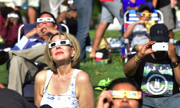 People wear solar eclipse glasses to view the partial eclipse from Beckman Lawn at Caltech in Pasadena, California on August 21, 2017.   Emotional sky-gazers stood transfixed across North America Monday as the Sun vanished behind the Moon in a rare total eclipse that swept the continent coast-to-coast for the first time in nearly a century. (Frederic J. Brown/AFP/Getty Images)