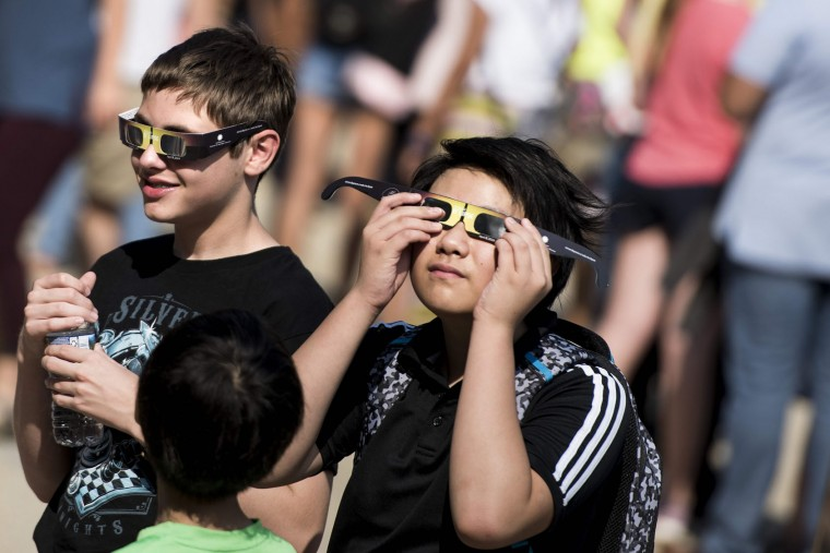 People test special solar glasses after getting them outside the Smithsonian's Air and Space Museum on the National Mall before an eclipse August 21, 2017 in Washington, DC. Skygazers across the United States awoke in excited anticipation Monday of witnessing the Sun briefly disappear, with the first total solar eclipse in 99 years to cast a shadow on the entire continent just hours away. (Brendan Smialowski/AFP/Getty Images)