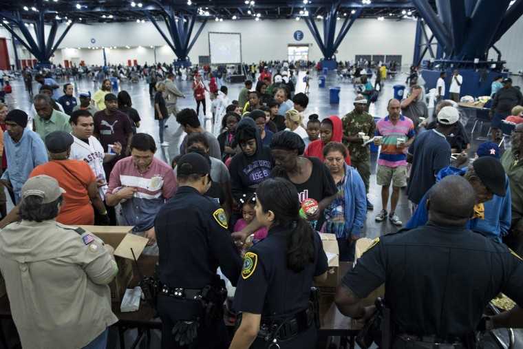 Flood victims gather for food at a shelter in the George R. Brown Convention Center during the aftermath of Hurricane Harvey on August 28, 2017 in Houston, Texas. (Brendan Smialowski/AFP/Getty Images)
