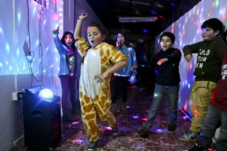 "In this July 22, 2017 photo, Selenna, sporting a giraffe costume for the fun of it, dances with other kids at the end of a gender identity workshop at a community center in Santiago, Chile. Selenna said she never liked celebrating her birthday because she would always get toy cars. ""Maybe they didn't notice it,"" said Selenna. ""But I was always (a girl)."" (AP Photo/Esteban Felix)"