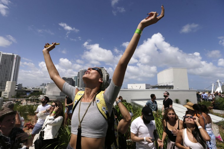 "A fashion designer who gave her name as ""Nonsense"" watches a total solar eclipse from the roof of the Phillip and Patricia Frost Science Museum, Monday, Aug. 21, 2017, in Miami. (AP Photo/Lynne Sladky)"