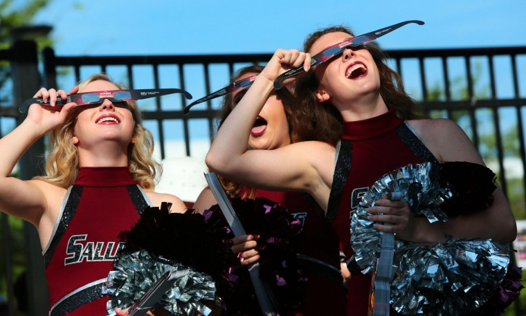Saluki cheerleaders try out eclipse glasses that they were giving out to visitors to Saluki Stadium on the campus of Southern Illinois University Carbondale, Ill., on Monday, Aug. 21, 2017. Scientists said Monday's total eclipse would cast a shadow that would race through 14 states including Illinois. (Robert Cohen/St. Louis Post-Dispatch via AP)