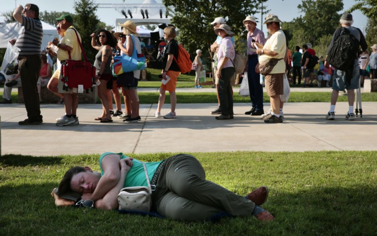 A woman takes a nap as people line up to enter Saluki Stadium for eclipse festivities on the campus of Southern Illinois University Carbondale on Monday, Aug. 21, 2017. (Robert Cohen/St. Louis Post-Dispatch via AP)