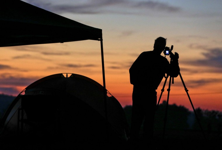 Jim Cleveland, of Shelbyville, Ky., sets up a camera at his campsite at sunrise as he prepares for the solar eclipse Monday, Aug. 21, 2017, on the Orchard Dale historical farm near Hopkinsville, Ky. The location, which is in the path of totality, is also at the point of greatest intensity. (AP Photo/Mark Humphrey)