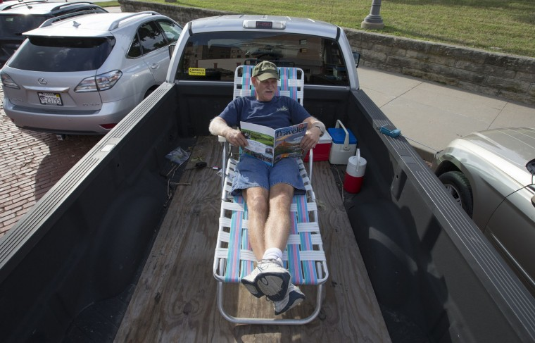 Chuck Willard of Council Bluffs, Iowa, reads a tourist magazine as he waits in the bed of his truck for the total eclipse in Falls City, Neb., Monday, Aug. 21, 2017. Willard, who works for Menards, blocked off this day many months in advance so he could view the eclipse. He decided to come to Falls City hoping the cloud cover here would be the lightest. (AP Photo/Nati Harnik)