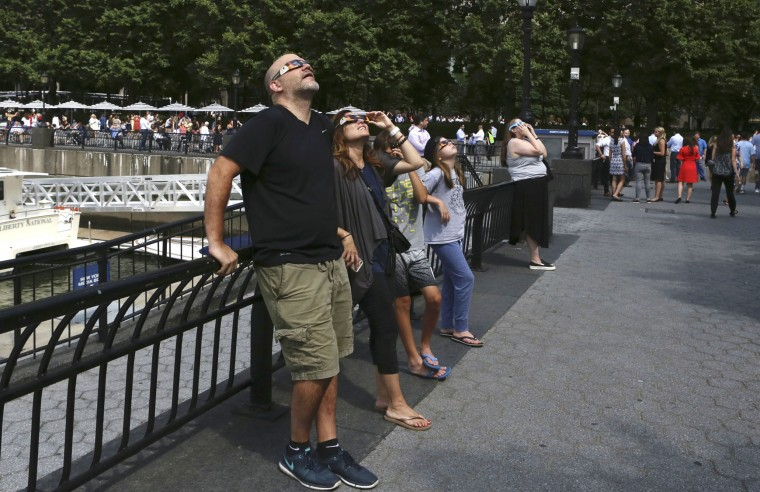 Spectators look up through eclipse viewing glasses at a partial phase of a total eclipse, Monday, Aug. 21, 2017, in New York. (AP Photo/Steve Luciano)