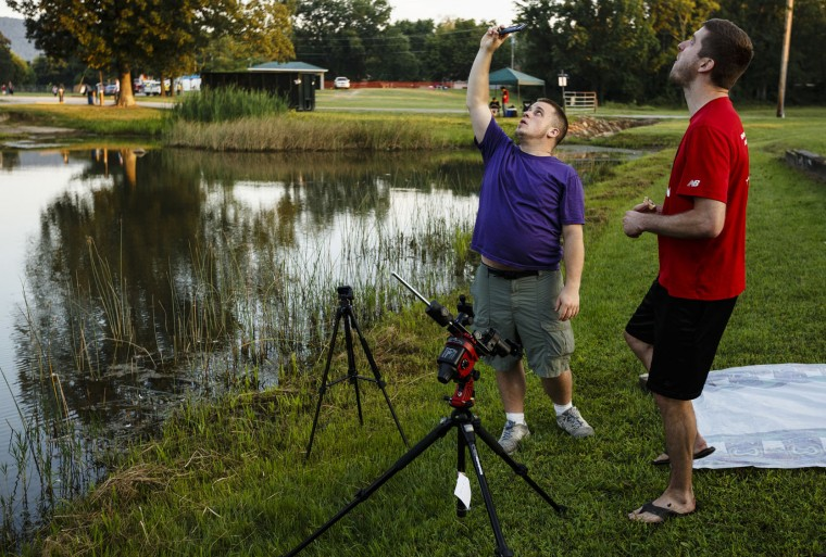Hunter Gnann, left, and Kevin Troy, from Wappingers Falls, N.Y., check the expected path of the sun as they set up in Veteran's Park to view the total solar eclipse on Monday, Aug. 21, 2017, in Spring City, Tenn. (Doug Strickland/Chattanooga Times Free Press via AP)