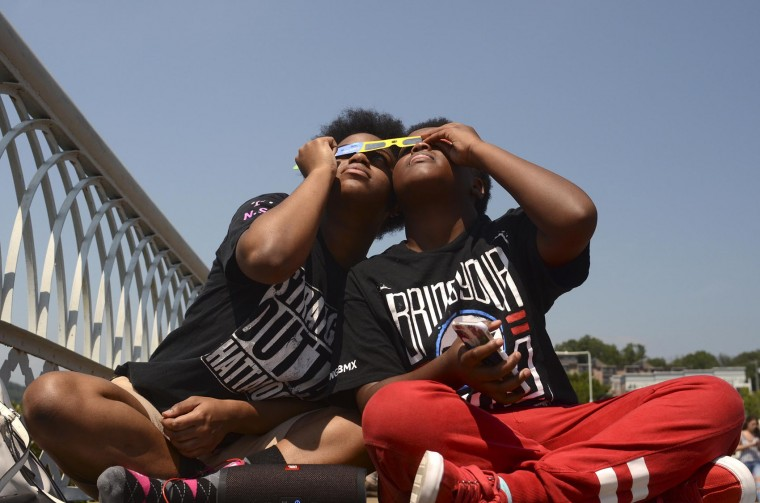 Photo by Robin Rudd From left, Kenya Williams and her cousin Kamau Mealing, both of Chattanooga, share their eclipse glasses in the last second of totality on Aug. 21, 2017. The cousins were joined by several hundred others on the Walnut Street Bridge in Chattanooga, Tenn. (Robin Rudd/Chattanooga Times Free Press via AP)