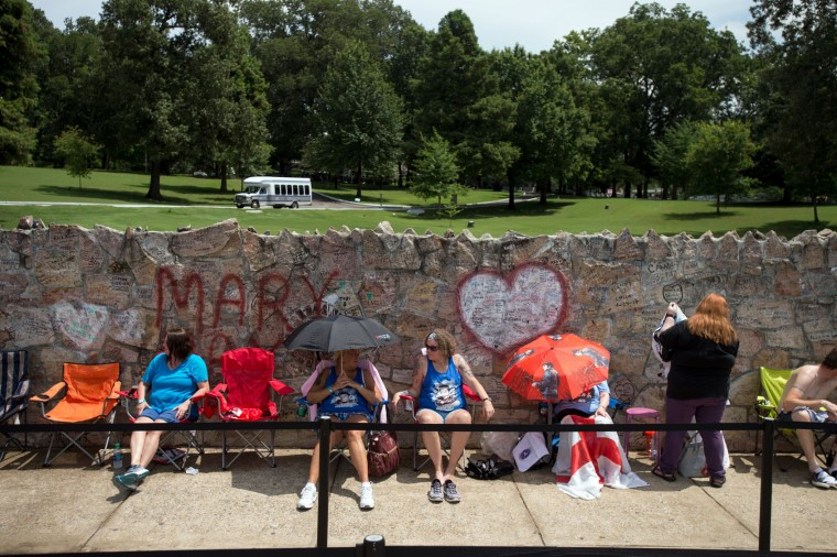 Fans wait in line outside Graceland, Elvis Presley's Memphis home, on Tuesday, Aug. 15, 2017, in Memphis, Tenn. Fans from around the world are at Graceland for the 40th anniversary of his death. Presley died Aug. 16, 1977. (AP Photo/Brandon Dill)