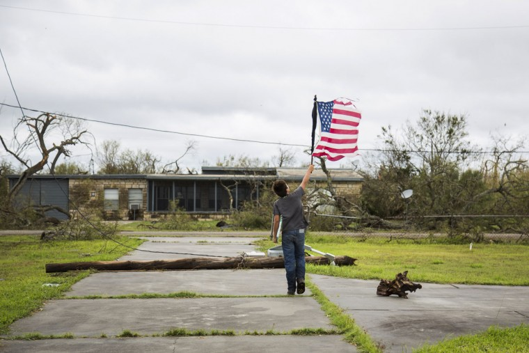 In this Sunday, Aug. 27, 2017 photo, Layton Carpenter walks down an empty driveway in Bayside, Texas, holding a broken American flag that he found in the water after Hurricane Harvey hit Bayside, Texas. (Olivia Vanni/The Victoria Advocate via AP)
