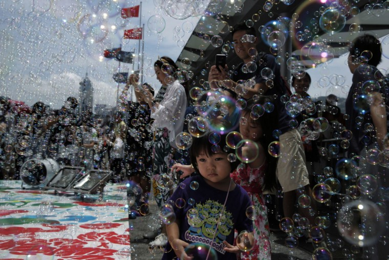 "A girl plays with bubbles during an art display ""Bubble Up"" created by Japanese artist Shinji Ohmaki in Hong Kong, Wednesday, Aug. 2, 2017. (AP Photo/Kin Cheung)"