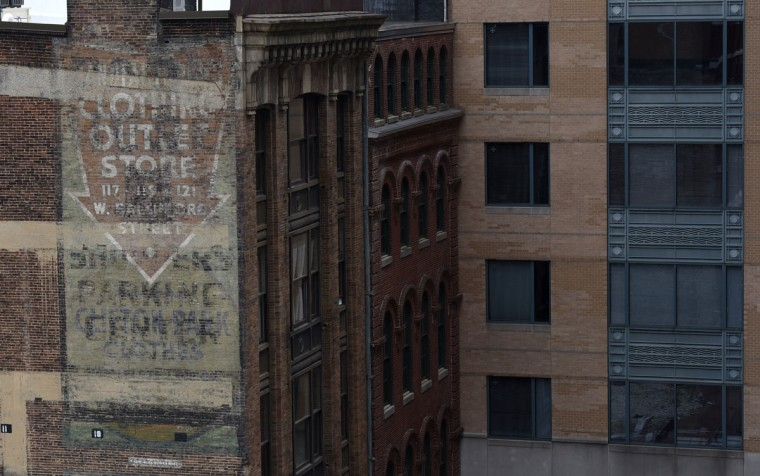 Overlapping ghost signs of several business on the side of a building on W. Baltimore Street. Clothing Outlet Store. Traces of old advertisements on buildings. (Kim Hairston/Baltimore Sun)