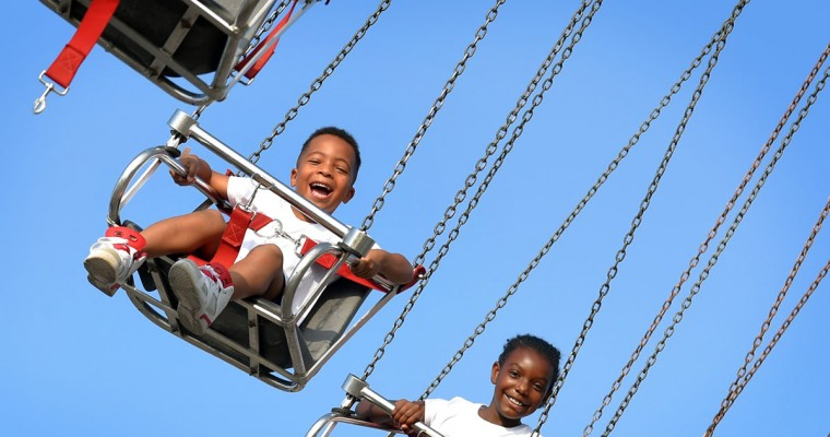 Caden Webb, 6, of Randallstown and Kennedy Satterfield, 8, of Woodlawn enjoy the Yoyo swing during Thurdsay's Ridemania event. (Lloyd Fox/Baltimore Sun)