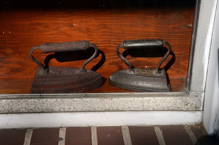 A pair of antique irons which were used for many years by the founder of TC Wing Laundry, are preserved in the laundry's front window.