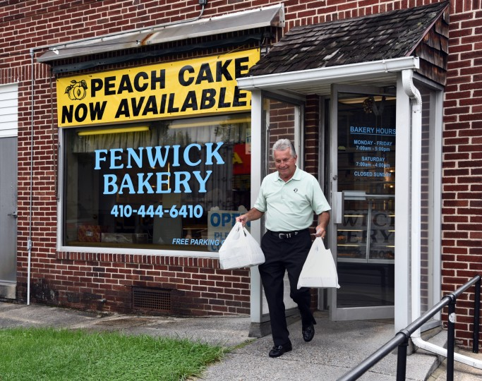 "Nick Schauman of Ocean City carries bags of peach buns and cakes, which he will share with his customers of DS Pipe and Steel.  He said he buys peach cakes every year at Fenwick Bakery, because they are the ""best in Baltimore.""  Fenwick has been making Baltimore peach cakes for many decades.  (Barbara Haddock Taylor/Baltimore Sun)"