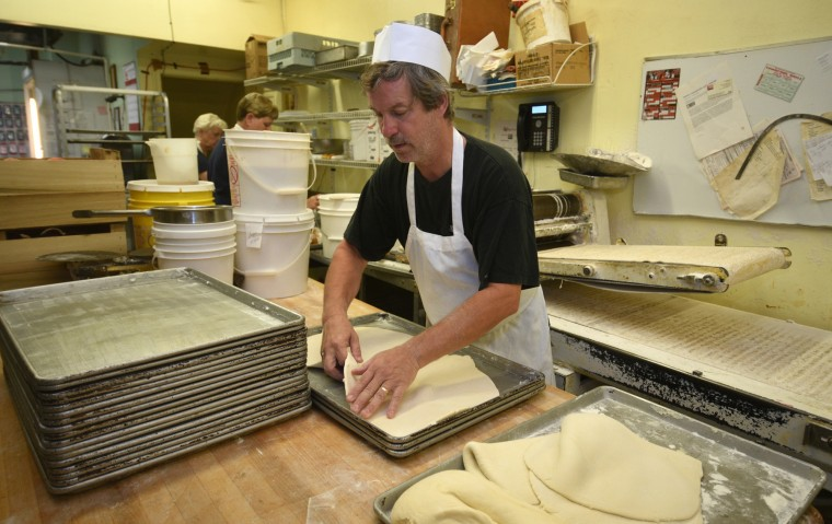 "Michael ""Al"" Meckel, co-owner, places sheets of dough on trays at Fenwick Bakery.  The dough will be covered with peaches and made into the bakery's traditional Baltimore summer treat, the Baltimore peach cake.  Mr. Meckel has been working at the bakery for 38 years.   (Barbara Haddock Taylor/Baltimore Sun)"