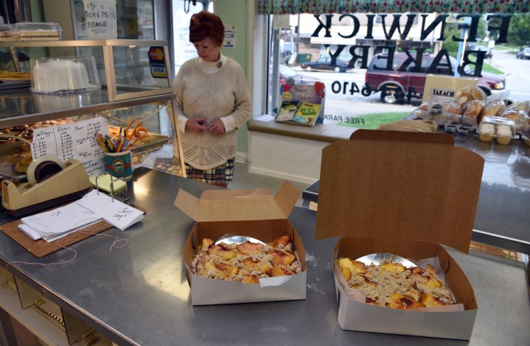 Pat Ozborn of Baltimore contemplates other baked goods as her peach cakes sit on the counter at Fenwick Bakery. Ms. Ozborn is taking the cakes to a party in New Jersey.  (Barbara Haddock Taylor/Baltimore Sun)