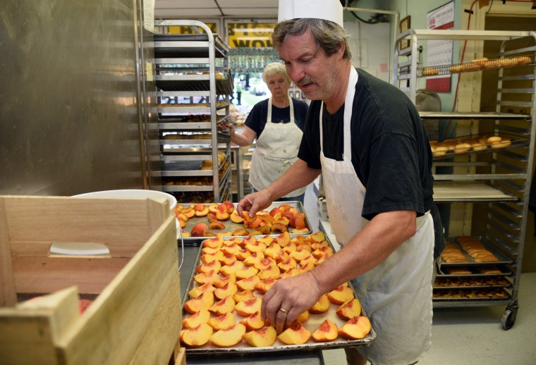 "Michael ""Al"" Meckel, co-owner, arranges peaches on a sheet of dough on a tray at Fenwick Bakery.  The dough will be covered with peaches and made into the bakery's traditional Baltimore summer treat, the Baltimore peach cake.  Mr. Meckel has been working at the bakery for 38 years.   (Barbara Haddock Taylor/Baltimore Sun)"