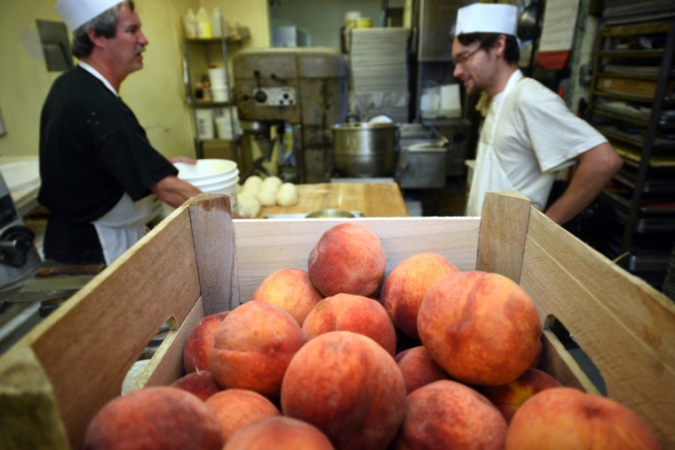 "Michael ""Al"" Meckel, left, co-owner, and baker apprentice Jeremy Collins, right, confer during peach cake making at Fenwick Bakery, which has been making Baltimore peach cakes for many decades.  (Barbara Haddock Taylor/Baltimore Sun)"