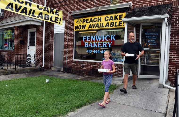 Ole Olson, right, and his granddaughter Laney Schollaert, 8, left, (both of Baltimore) walk out carrying peach cakes at Fenwick Bakery. (Barbara Haddock Taylor/Baltimore Sun)