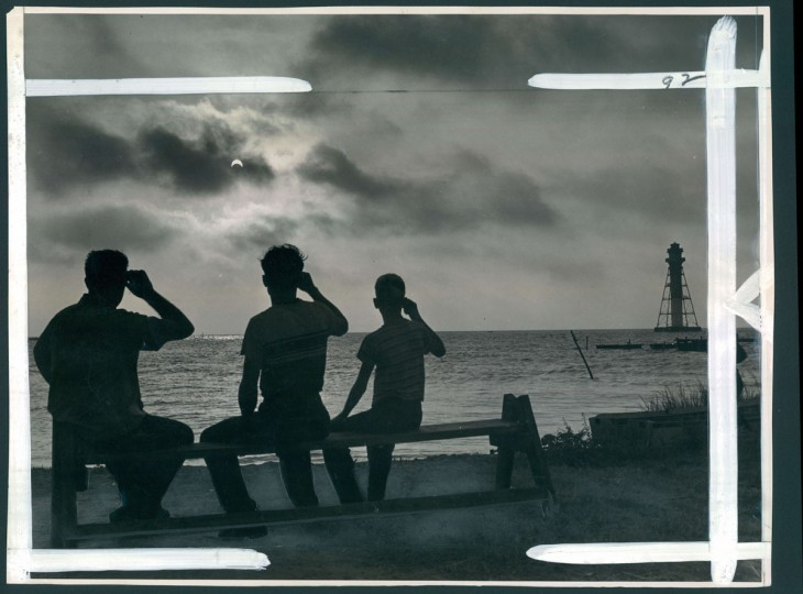 September 1, 1951 - WATCHING THE ECLIPSE -- This is how the eclipse looked at 7:12 this morning at Miller Island. Watching are (left to right) Clair Byroade, Thomas Walden and Gerald Byroade. The Miller Island light is at extreme right. About 92 percent of the sun was blocked out by the moon. Photo taken by Baltimore Sun Staff Photographer Robert F. Kniesche.