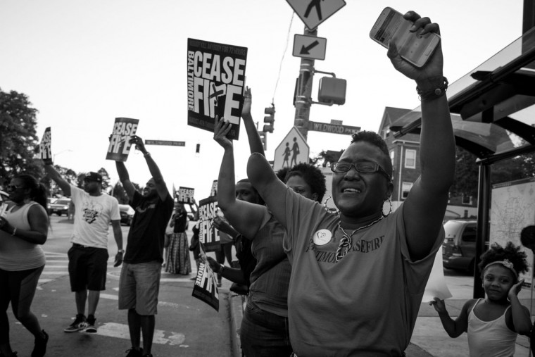 "Baltimore, MD -- 8/4/2017 -- Erricka (cq) Bridgeford (right), organizer of Baltimore Ceasefire and rally supporters standing on the street promoting Ceasefire message to on coming traffics. Day 1 of the 72 hours Baltimore Ceasefire. ""Stop the Violence Rally"" located on Edmondson Avenue and Wildwood Parkway, where approximately 75 local Baltimore city residents came out to promo the Ceasefire message. (Photo and caption by Paul Lai)"