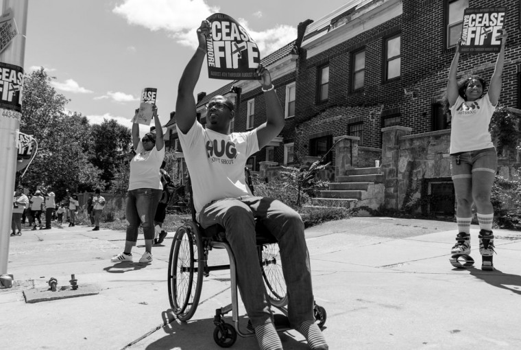 Baltimore, MD -- 8/5/2017 -- William Thomas (center) from Baltimore was shot in 2004 resulting in him being on the wheelchair, he hopes his action can pay forwards to the city for all the supports he received from the people around him. Day 2 of the 72 hours Baltimore Ceasefire. HUG DON'T SHOOT groups march from Druid Hill Park to Pennsylvania Avenue and North Avenue. Supporters gives out countless hugs and water to local Baltimore city residents. (Photo and caption by Paul Lai)